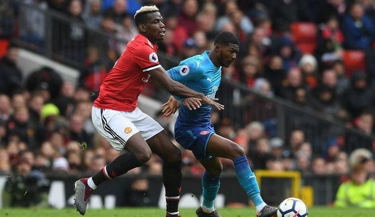 Ainsley Maitland-Niles saat berduel dengan Paul Pogba dalam laga Manchester United vs Arsenal musim lalu.
